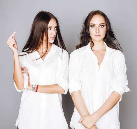 two sisters twins posing, making photo selfie, dressed same white shirt, diverse hairstyle friends