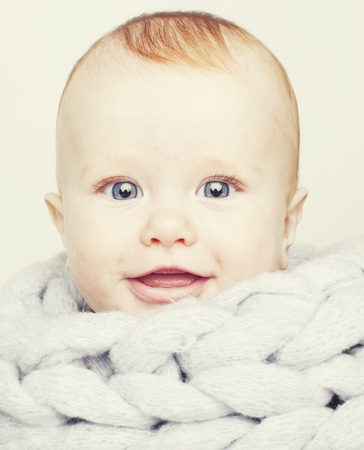 little cute red head baby in scarf all over him close up isolated, adorable kid smiling