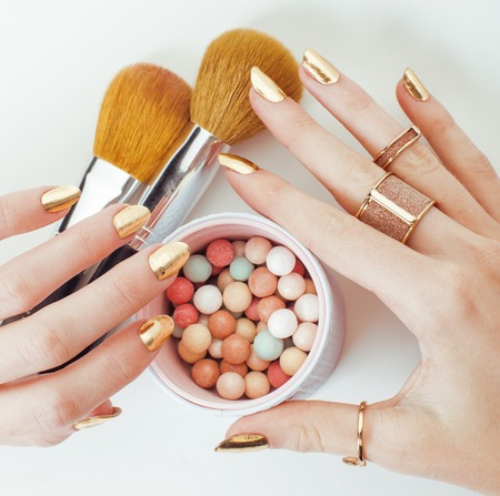 manicure nails: woman hands with golden manicure and many rings holding brushes, makeup artist stuff stylish, pure close up bright