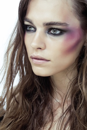beaten up: young beauty woman with makeup like shiner on face close up isolated  white background