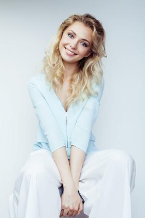 sonriente: bastante joven mujer rubia sonriente sobre fondo blanco close up maquillaje Foto de archivo