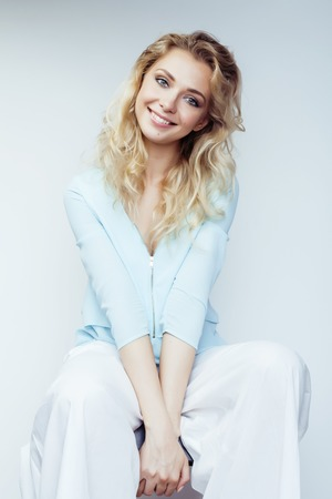 rubia: bastante joven mujer rubia sonriente sobre fondo blanco close up maquillaje Foto de archivo