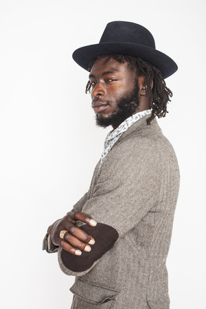 young handsome afro american boy in stylish hipster hat gesturing emotional isolated on white background
