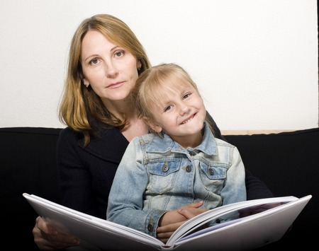 storytelling: mature woman with daughter reading book at home