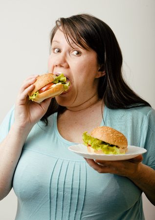fat food: fat woman having choice between hamburger and salad Stock Photo