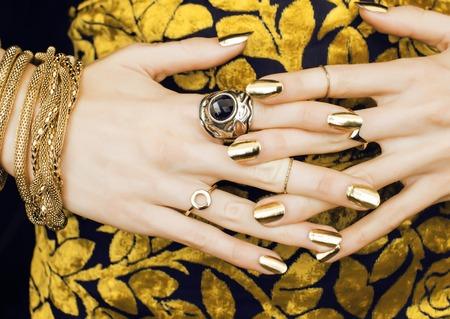 vrouw handen met gouden manicure veel sieraden op fancy dress close up