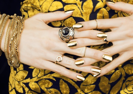 woman hands with golden manicure lot of jewelry on fancy dress close up Stock Photo