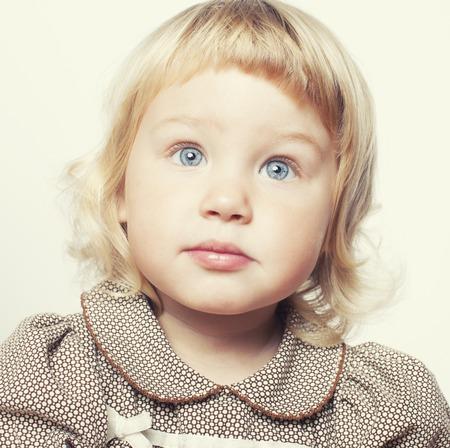 klein schattig blond meisje close-up geïsoleerd op witte achtergrond