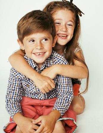 gemelos ni�o y ni�a: peque�o muchacho lindo y ni�a abrazos jugando en el fondo blanco