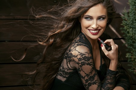 flying hair: beauty smiling rich woman in lace with dark red lipstick, flying hair close up make up