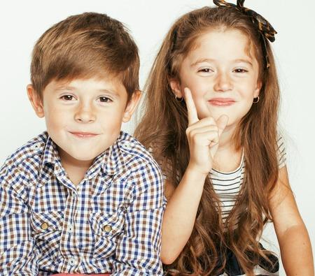 gemelos niÑo y niÑa: pequeño muchacho lindo y niña abrazando juega en el fondo blanco, sonriendo familia feliz Foto de archivo