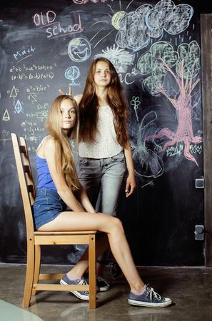 salon de clases: regreso a la escuela despu�s de las vacaciones de verano, las ni�as de dos adolescentes reales en el aula con pizarra pintada juntos