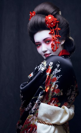 young pretty real geisha in kimono with sakura and decoration