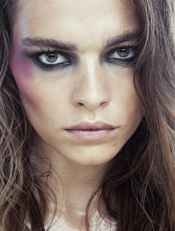 beaten: young beauty woman with makeup like shiner on face close up isolated white background, scary junky