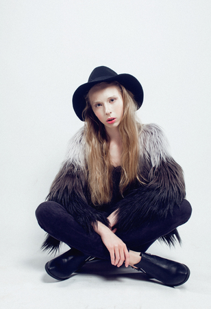 blonde teenage girl: young blonde teenage girl in hat and fur coat, fashion dressed model, studio shot hipster