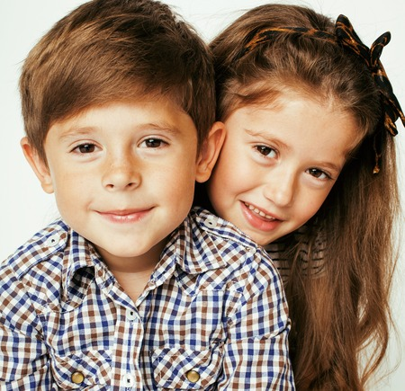 two girls hugging: little cute boy and girl hugging playing on white background, happy family close up isolated
