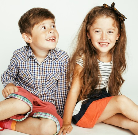 gemelos niÑo y niÑa: pequeño muchacho lindo y niña abrazando juega en el fondo blanco, familia feliz cerca aisladas Foto de archivo
