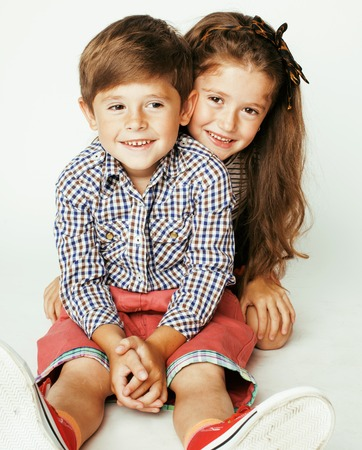 gemelos ni�o y ni�a: peque�o muchacho lindo y ni�a abrazando juega en el fondo blanco, familia feliz cerca aisladas Foto de archivo