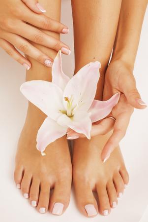 pedicura: manicura pedicura piernas de la mujer con cierre de la flor del lirio arriba aislado en el blanco perfecto