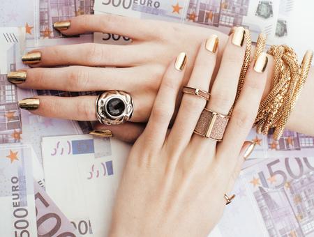 donna ricca: mani di donna ricca con il manicure d'oro e molti anelli gioielli su euro in contanti da vicino cinquecento Archivio Fotografico