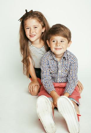 gemelos ni�o y ni�a: peque�o muchacho lindo y ni�a abrazando juega en el fondo blanco, feliz gemelos sonriendo familia Foto de archivo