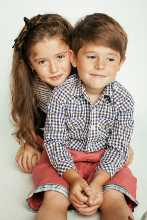 gemelos niÑo y niÑa: pequeño muchacho lindo y niña abrazando juega en el fondo blanco, feliz gemelos sonriendo familia Foto de archivo