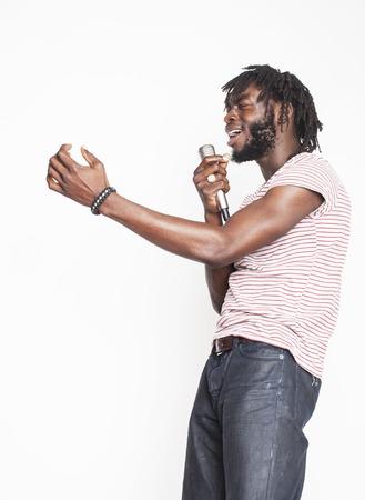 感情的な動きをすぐに笑顔で身振りで、白い背景で隔離のマイクを使って歌っている若いハンサムなアフリカ系アメリカ人の男の子