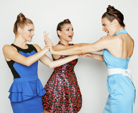 three elegant fashion woman fighting on white background, bright dresses evil faces