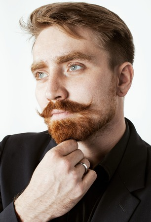 redhaired: young red hair man with beard and mustache in black suit on white background close up