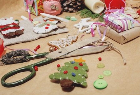 craft background: handmade christmas gifts in mess with toys, candles, fir, ribbon wooden vintage