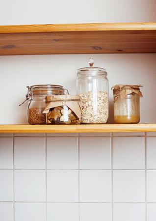 alimentacion balanceada: real comfort wooden kitchen with breakfast ingredients close up in glass, honey, oatmeal, milk, muesli morning