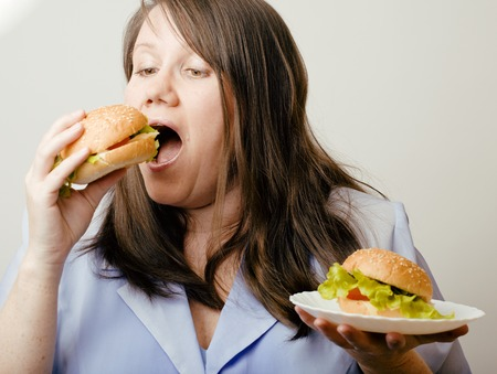 obsessive: fat white woman having choice between hamburger and salad emotional