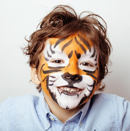 makeup a brush: little cute boy with faceart on birthday party close up, little cute orange tiger