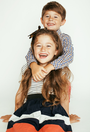 little cute boy and girl hugging playing on white background, happy family smiling close up 免版税图像