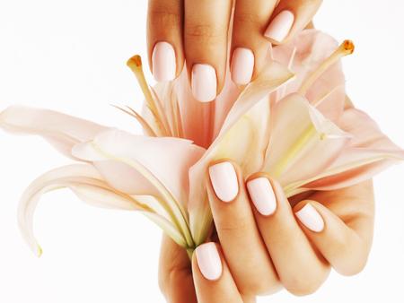 schoonheid delicate handen met manicure houden bloem lelie close-up geïsoleerd op wit perfecte vorm Stockfoto