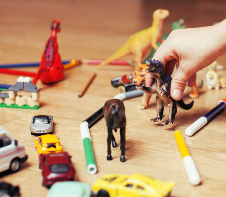 free education: children playing toys on floor at home, little hand in mess, free education, happy childhood