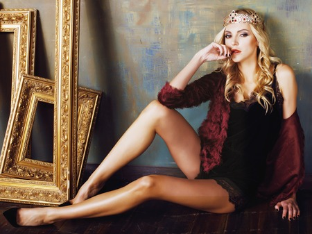 young blond woman wearing crown in fairy luxury interior with empty antique frames total wealth vintage Standard-Bild