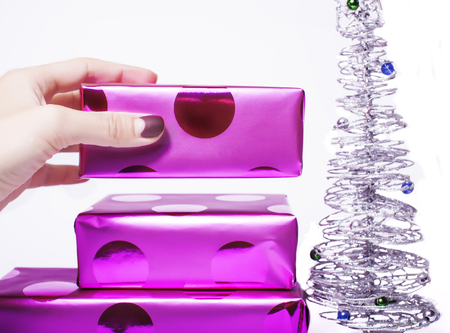 christmas manicure: woman manicured hand puting christmas gift to rest pile of purple gifts close up isolated silver little tree cute stylish manicure