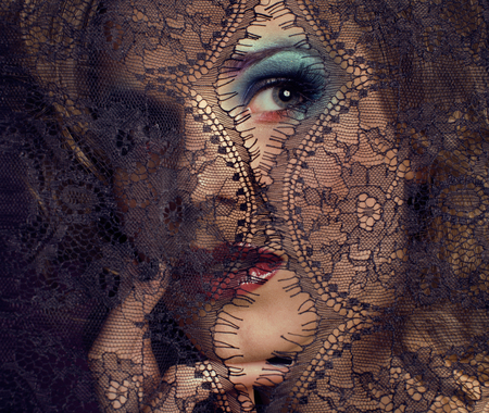 mistery: portrait of beauty young woman through lace close up mistery makeup