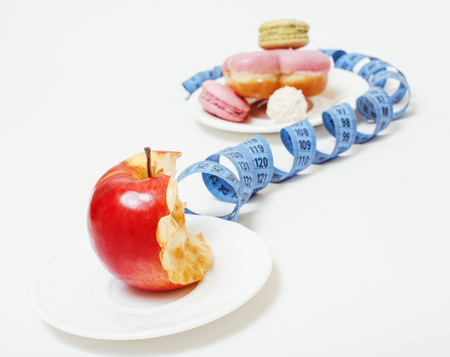 eating questions: new diet concept, question sign in shape of measurment tape between red apple and donut isolated on white