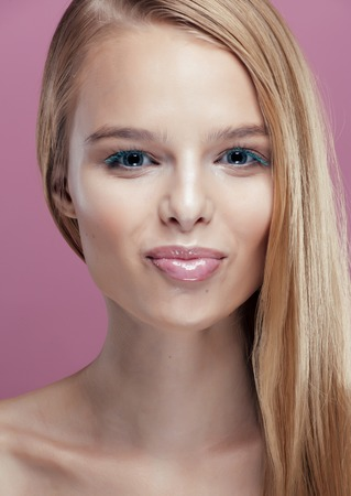 barbie: young pretty blonde real woman with hairstyle close up and makeup on pink background smiling