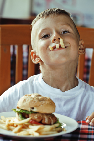 children eating: little cute boy 6 years old with hamburger and french fries making crazy faces in restaurant close up