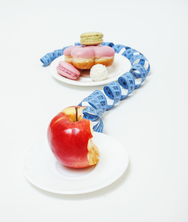 eating questions: new diet concept, question sign in shape of measurment tape between red apple and donut, cake, macaroon isolated on white