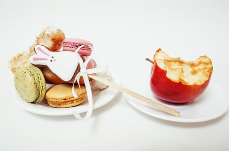 donut shape: new diet concept, question sign in shape of measurment tape between red apple and donut, cake, macaroon isolated on white