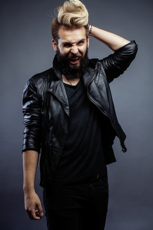 facial gestures: young attractive bearded hipster man gesturing emotional screaming in studio sucsess modern