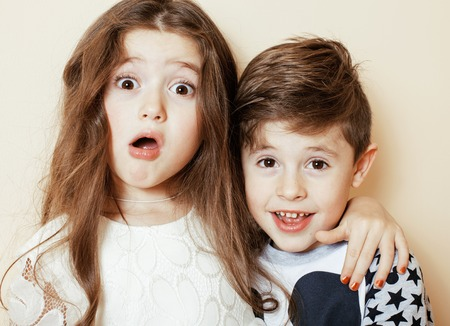 friends hugging: little cute boy and girl hugging playing on white background, happy family smiling brother and sister