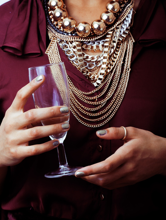 make a gift: young african-american woman drinking champagne, holding glass, wearing lot of golden jewelry close up