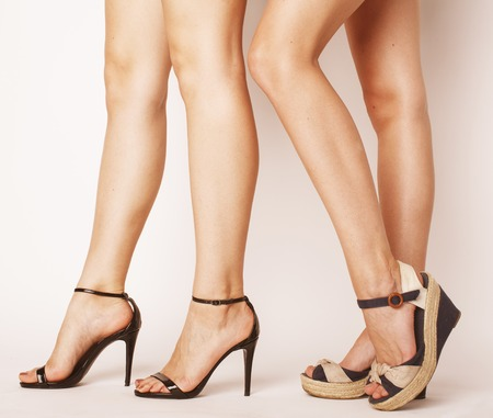 dos pares de piernas de la mujer en tacones hight zapatos aislados en blanco
