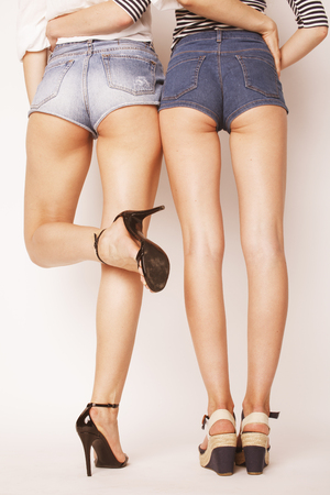 booty shorts: legs of young women, pair of butts in jeans shorts isolated on white
