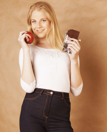 habbit: young beauty blond teenage girl smiling, choice between sweet and red apple Stock Photo